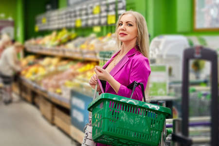Woman with a shopping basket stands in supermarket.