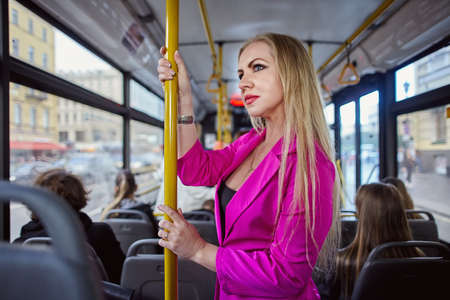 Woman in pink inside a trolleybus or bus. A public transport passenger holds onto the handrails. 免版税图像