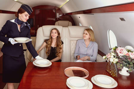 Cabin crew serving passengers inside the corporate jet. The flight attendant serves the table for those flying in business class.