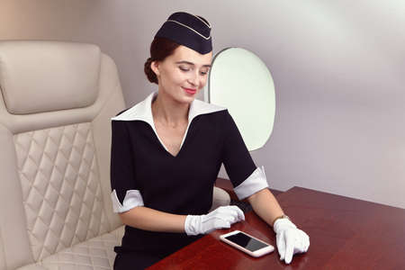A flight attendant on board a corporate flight. An air stewardess sits in the seat of a private jet. Archivio Fotografico