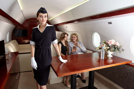 Passengers and air hostess inside a corporate plane. Archivio Fotografico