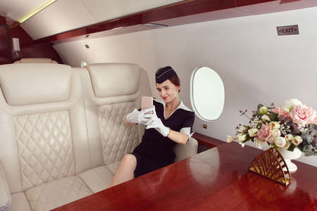 A flight attendant takes a selfie in the first class cabin inside the plane.