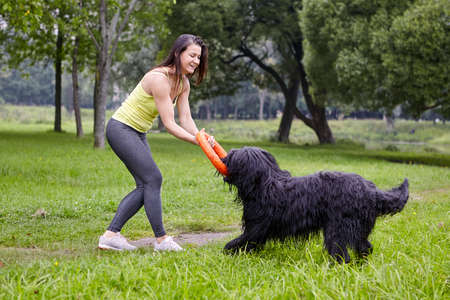 Woman plays with black briard and smiling in city garden at daytime. Stock Photo