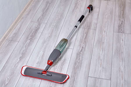 Flat spray mop with water spraying of wooden floor cleaner with trigger spray on handle and microfiber pad. Stock fotó