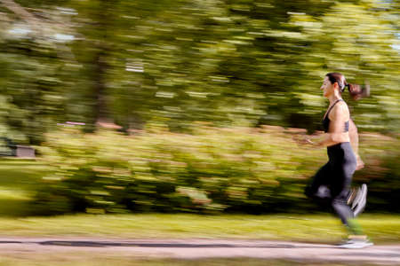 Blurred motion of woman who is running in the public park. Active white female is training in city garden at summer. Standard-Bild