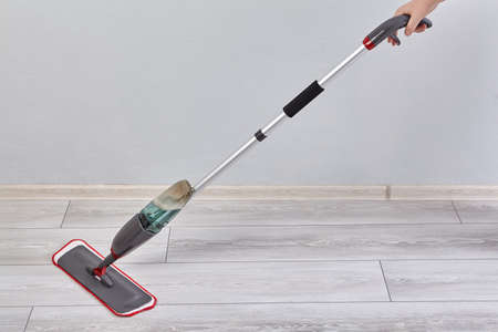 Flat mop with spray and microfiber head is cleaning laminate floor in the room from dust and dirt.
