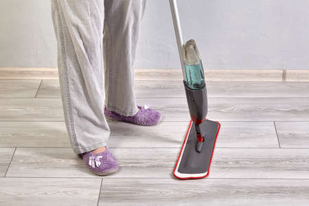 The cleaning lady is washing floor in the apartment with help of flat mop with spray and microfiber head. Cleaning laminate from dust and dirt. Stock fotó