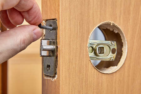Locksmith installs door knob with lock. An Carpenter pushes standard rectangular faceplate, slide the latch into place with the bevel facing the doorjamb and secure with the two short screws.