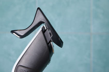 Front part of hair clipper with nozzle on tile background in bathroom.