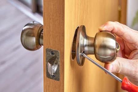DIY installation of door lock mechanism with handles in new wood panel.