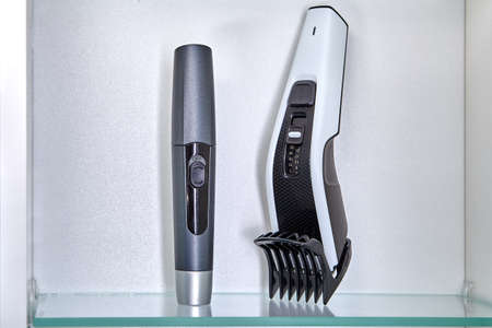 Clipper and trimmer to remove hair in nose are on shelf in locker of bathroom. Standard-Bild