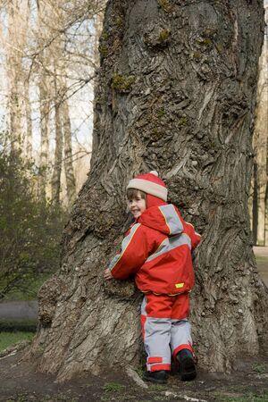 vejez: ni�a en ropa roja cerca de tronco de �rbol de vejez
