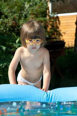 The little girl is going to bathe in pool photo