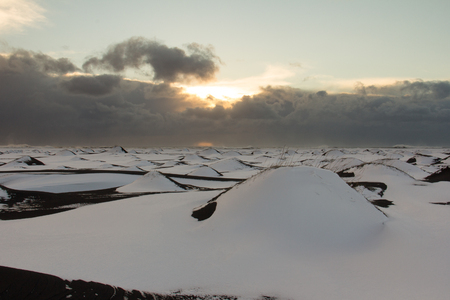 Snow covered sand dunes on an Icelandic black beach on the south coast near Vik. A storm is coming in during sunset.