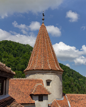 A turret of Bran Castle also known as Draculas Castle under a blue sky Editöryel