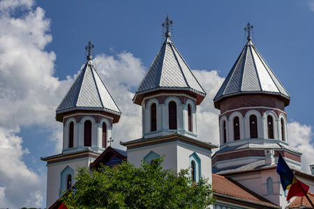 Details of the ornate cupolas on an orthodox church in the village of Blăjel, Romania under a blue sky