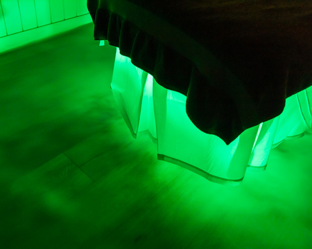 An eerie green glow and mist is coming from under a bed with a white skirt and dark duvet