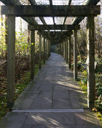 A stone path under a pergola curves to the left in the distance
