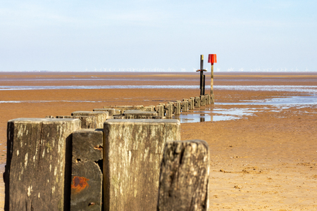 Wooden groyne curves into the distance terminating in a warning beacon at low tide on the Humber Estuary at Cleethorpes beach, Lincolnshire, England, United Kingdom with wind turbines in the distance