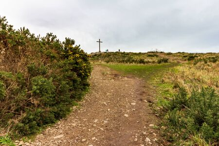 A rocky path leading toward the cross located high atop Bray Head in County Wicklow, Ireland Stock Photo
