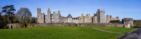 Panoramic photo of Ashford Castle, now a luxury hotel, taken from the shore of Lough Corrib Фото со стока