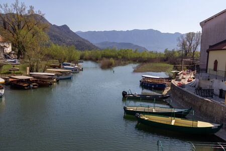 In Virpazar, Montenegro an inlet of Skadar Lake contains multiple tour boats waiting for passengers