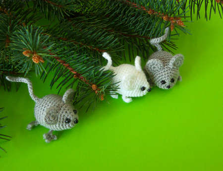 little toy mice with Christmas tree on a green background. New Year