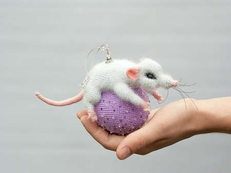 Gray toy mouse on a lilac ball, symbol of the new year.