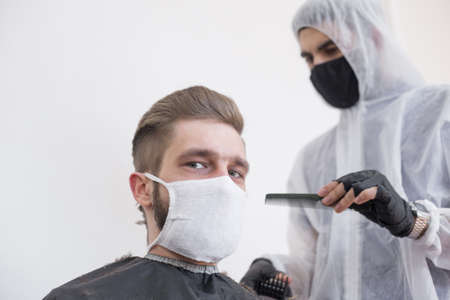 The work of the barber during the coronavirus, the hairdresser trim the client in a mask and a protective suit, quarantine