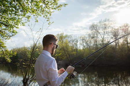 A man fishing in a business suit, in a white shirt and tie Stock Photo