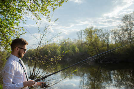 A man fishing in a business suit, in a white shirt and tie