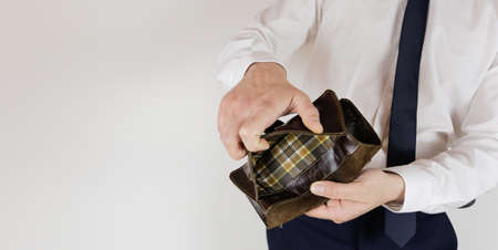 A man in a business suit holds in his hands an empty wallet without money. Financial crisis. Bankruptcy in business. The employer is disappointed.