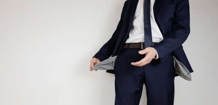 A man in a business suit turned his pockets inside out. Financial crisis. Bankruptcy in business. An entrepreneur without money. Archivio Fotografico