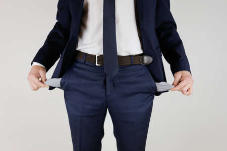 A man in a business suit turned his pockets inside out. Financial crisis. Bankruptcy in business. An entrepreneur without money. Stok Fotoğraf