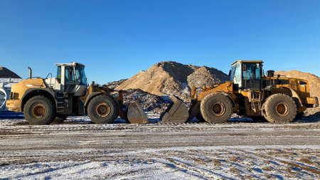 Sand quarry, excavating equipment, two yellow bulldozers before work in sunny morning on sand background