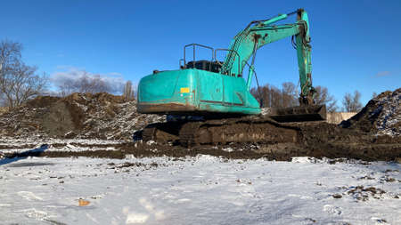 green excavator stay in the mud in sunny day Stock Photo