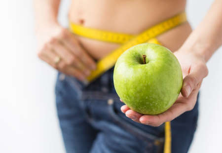 Woman measuring her waistline and showing fresh green apple in hand photo