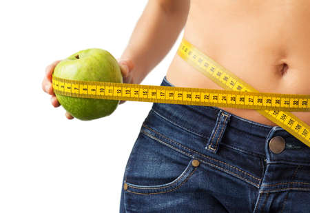 Woman measuring her waistline and holding fresh green apple in hand Imagens