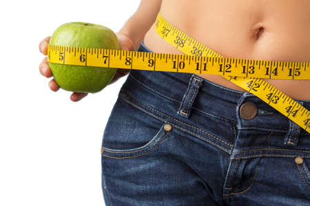 'flat stomach': Woman measuring her waistline and holding fresh green apple in hand Stock Photo