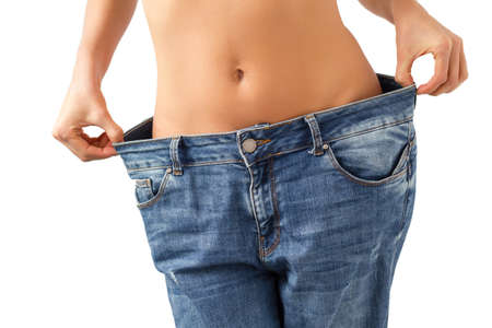 Weight loss concept - slim woman is happy to show her big old jeans