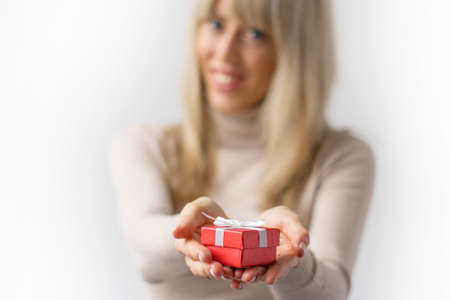Woman presenting small red gift in box photo