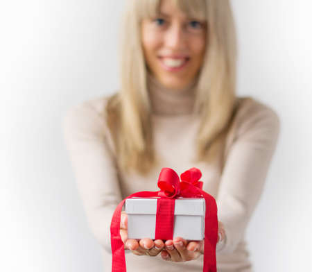 Out of focus woman holding white present box with red ribbon photo