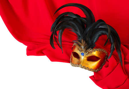 Venetian mask with black feathers on red fabric photo