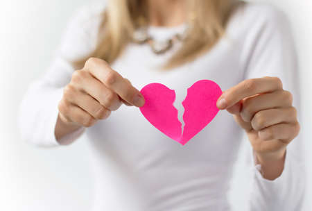 relationship breakup: Woman symbolically tearing up pink paper heart