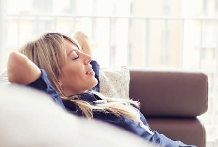 relaxed woman: Relaxed young woman lying on couch Stock Photo