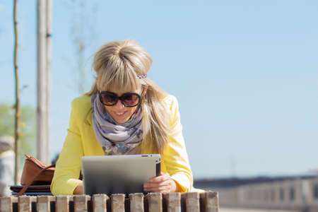 reader: Woman using tablet computer outdoors Stock Photo