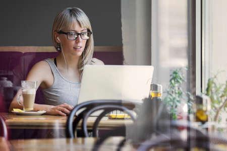 若い女性のカフェのコンピューターでの作業