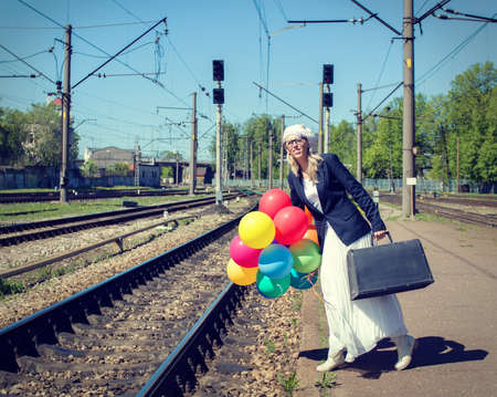 Young woman with colorful balloons standing on railway platform photo