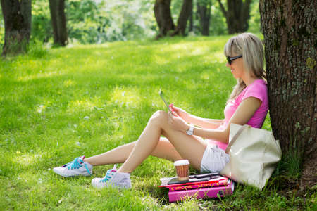 Relaxed young woman using tablet computer outdoors photo