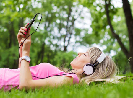 Young woman listening to music while lying down on grass photo